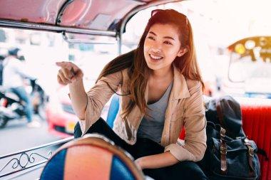 Young woman sitting at tuk tuk in Bangkok, Thailand