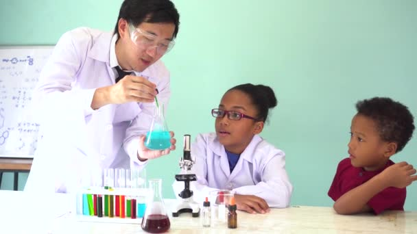 Young scientist holding a flask and teaching two African American mixed kids in chemistry lab experiment