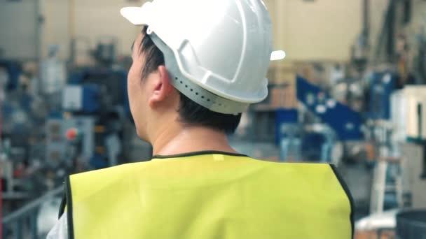 Výrobní pracovník s bezpečnostním pevným kloboukem procházkové prostřednictvím průmyslových zařízení