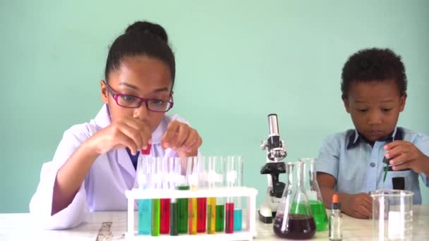 Two African American mixed kids testing chemistry lab experiment