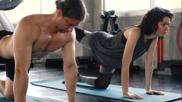 Young woman and man practicing yoga with Moon Bird Pose Yoga or Chakorasana on the gym floor. Two people couple working out indoors.