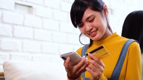 20-letá asijská žena držící kreditní kartu a mobilní telefon v útulném bílém pokoji