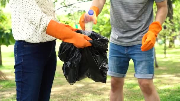 Group of volunteers with gloves collecting garbage waste into trash bag in park