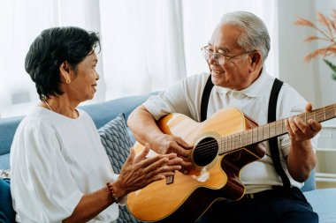 Asian senior couple sitting on the sofa and playing acoustic guitar together. Happy smiling elderly woman clapping hands while old 70s guitarist husband singing. Enjoying retirement life at home.