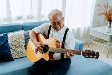 Asian senior man sitting on the sofa and playing acoustic guitar. Happy smiling elderly singing and enjoying with guitar. Enjoying retirement life at home.