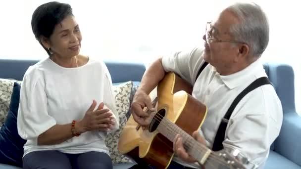 Ázsiai végzős pár ül a kanapén és együtt akusztikus gitároznak. Boldog mosolygós idős nő tapsol, míg az öreg 70-es évekbeli gitáros férj énekel. Élvezi a nyugdíjas életet otthon.