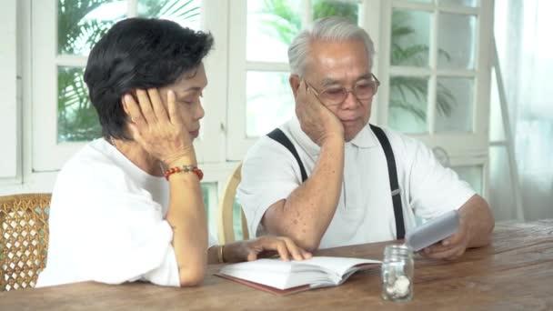 Asijské starší pár zdůraznil a vážné počítání s kalkulačka a mají problém s penězi
