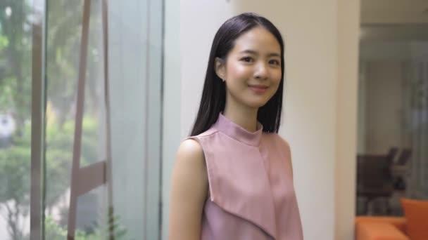 Fiatal ázsiai üzletasszony, összehajtogatott karokkal az irodaházban. Kínai Koreai Ázsia okos hölgy karokkal keresztbe portré videó
