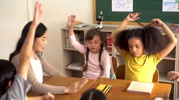 Asijské školní učitel se studenty zvedá ruce