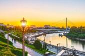 Nábřeží řeky s schodiště a pouliční osvětlení na letní západ slunce