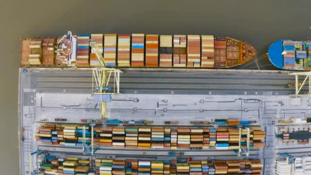 Luftaufnahme von der Höhe des Hafendocks, vertäut Frachtschiff kommt aus dem Ozean in Erwartung der Entladung von Containern