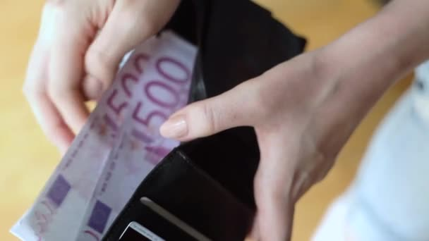 Closeup of woman hands holding a wallet counting new euro banknotes