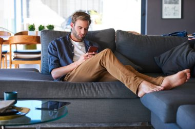 caucasian man busy texting while sitting in a modern home