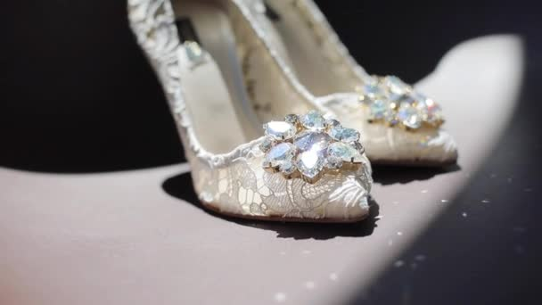 Female white lace design shoes with shiny diamonds standing close up indoors on dark background text. Wedding luxury footwear with precious stones rack focus shining on floor. Bridal fashion designer