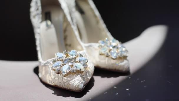 Bílé krajkové značkové boty pro ženy stojící uvnitř zářící diamanty drahé kameny zpomalené. Ženské svatební obuv čeká princezna černé pozadí zblízka kopie prostor. Svatební móda