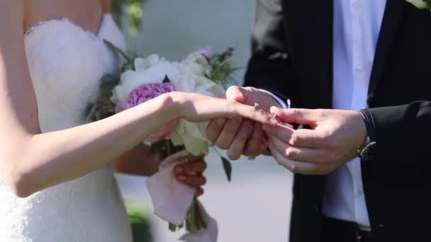 Bräutigam putting Ehering am Finger Bräute hautnah Sommertag kein Gesicht Zeitlupe festliche Kleidung. Nicht erkennbare Mann klingelt Frau Verlobter Designerschmuck Luxus-Lifestyle. Brautmode