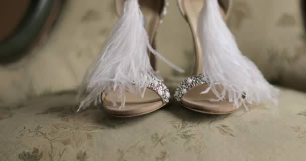 Woman designer shoes close up feather diamonds high heels shallow dof 4k indoors. Beautiful pair of  white stylish luxury bridal footwear standing in vintage interior furniture. Fashion design
