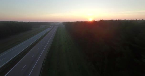 4 k drone létání nad Dvouproudá silnice dálnice při západu slunce paprsky lesa lesní večerní světlo. Letecký pohled po dálnici dálnice s automobily řízení. Nákladní dopravu přepravní průmysl