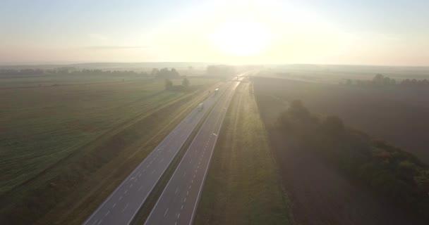 4 k letecký pohled na silnici highway s každodenní dopravní přepravy v sunrise mlhavé ráno světelného pole. Létání nad Dvouproudá silnice v krajině s nákladní auta se pohybují. Autodopravu nákladní logistiky