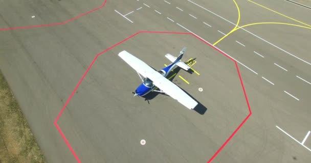 4k Luftbildaufnahme, die ein kleines einmotoriges Flugzeug zoomt, das von oben auf der Landebahn steht. Draufsicht auf ein Privatflugzeug, das auf Passagiere im Asphalthintergrund des Flughafens wartet. Weltreise-Urlaub