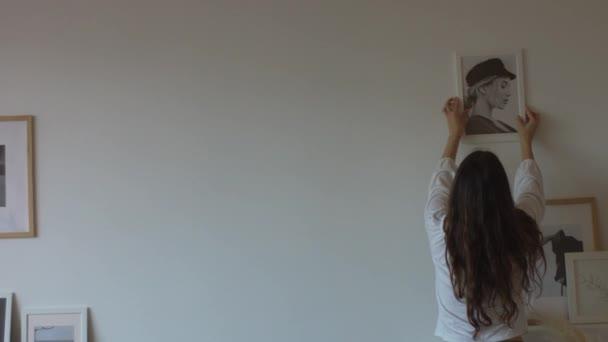 fröhliche Mädchen hängen Bilder an weißen Wänden drinnen Innenrückseite 4k Handkamera. langhaarige Frau dekoriert Zimmer mit Fotomalereien kopieren Raum Text. Design Wohndekoration Kunst neue Wohnung