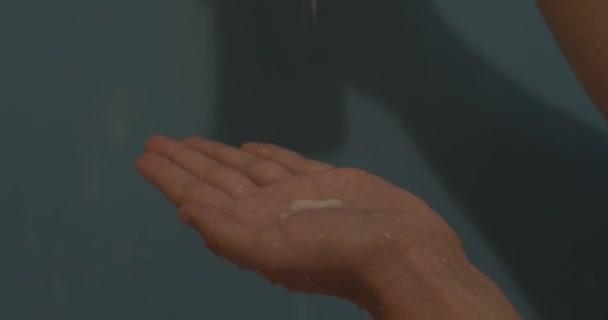 Női öntés sampon, balzsam, maszk, tejszín, kozmetikai folyékony kéznél zuhany. Vízcseppek kézzel, kozmetikai folyékony kék háttér közelről