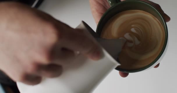 Barista Pouring Milk Into Cup Of Espresso To Make Latte Art Close-up. Professional Coffeemaker Drawing Latte Or Cappuccino Art On Coffee With Soy Milk. Process Of Making Lactose Free Drink In Cafe