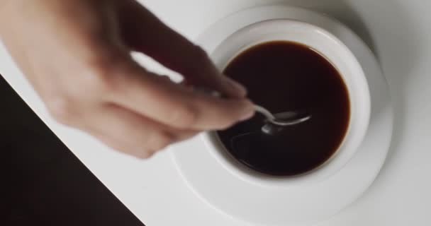 Top View Of Hand Stirring Sugar In Cup Of Hot Coffee With Spoon On White Table. Drinking And Enjoying Delicious Coffee Americano From White Cup. Beautiful Close-up View Of Morning Coffee In Cafe