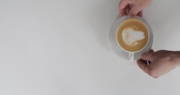 Top view of faceless waiter serving cappuccino to woman inside cafe natural light. Male hands putting white cup with coffee on table and girl taking it slow motion. Restaurant  street food lifestyle