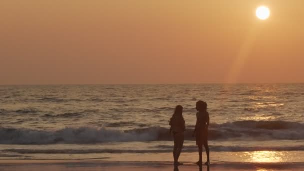 Happy couple with little baby on hands spending leisure time together enlightened with setting sun. Unrecognizable family walking at seaside beach slow motion copy text space. Close relations summer