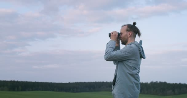 Side portrait of Caucasian man with bun holding binoculars outdoors green field background. Bearded tourist looking through field-glass observing wild animals handheld device. Nature fauna hobby