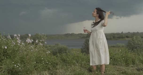 Elegantní dívka hladí dlouhé vlasy na letním větru deštivé krajiny pozadí. Mladá žena v bílých šatech, stojící sama na přírodě, zpomaluje kopírování prostoru. Změnit koncepci svobody
