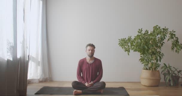 Bärtiger Mann sitzt im Schneidersitz auf Yogamatte und übt Pranayama mit geschlossenen Augen. Junge kaukasische Yogi-Meister machen Atemübungen in Innenräumen mit natürlicher leichter Zeitlupe. Gesunde Lebensgewohnheiten