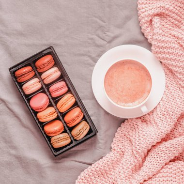 Bed with pink knitted plaid, coffee and macaroons.