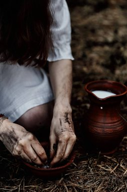 A woman in a white witch dress rips dry herbs over ceramic brush for spells and potions. Horror themes. Halloween.