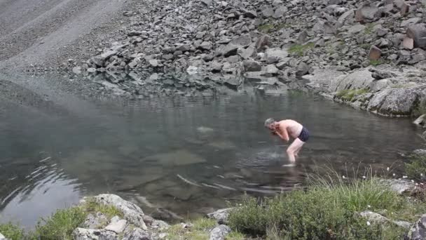 Undressed man washing his face in a lake, Mountain Spirits of the Lake, Altai Mountains, Russia