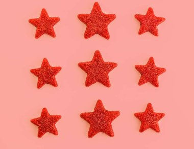Nine red stars on pink background. Flat lay. View from above. Day of the defender of Fatherland. The day of Soviet and Russian Armies.