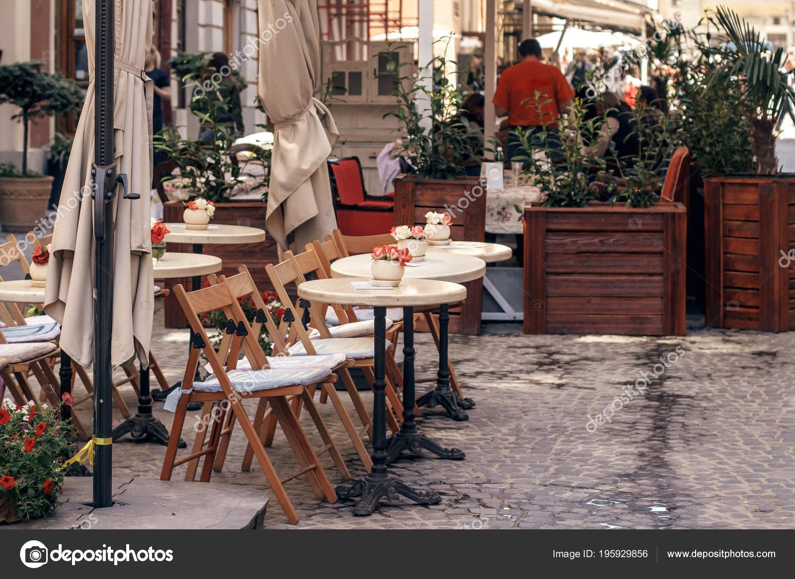 Mooie café terras met weinig vintage tafels houten stoelen planten