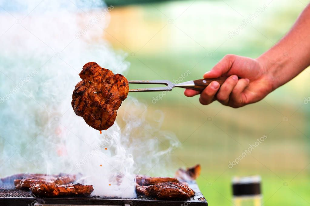 Meat pork steak on a hot grill BBQ with smoke and fire