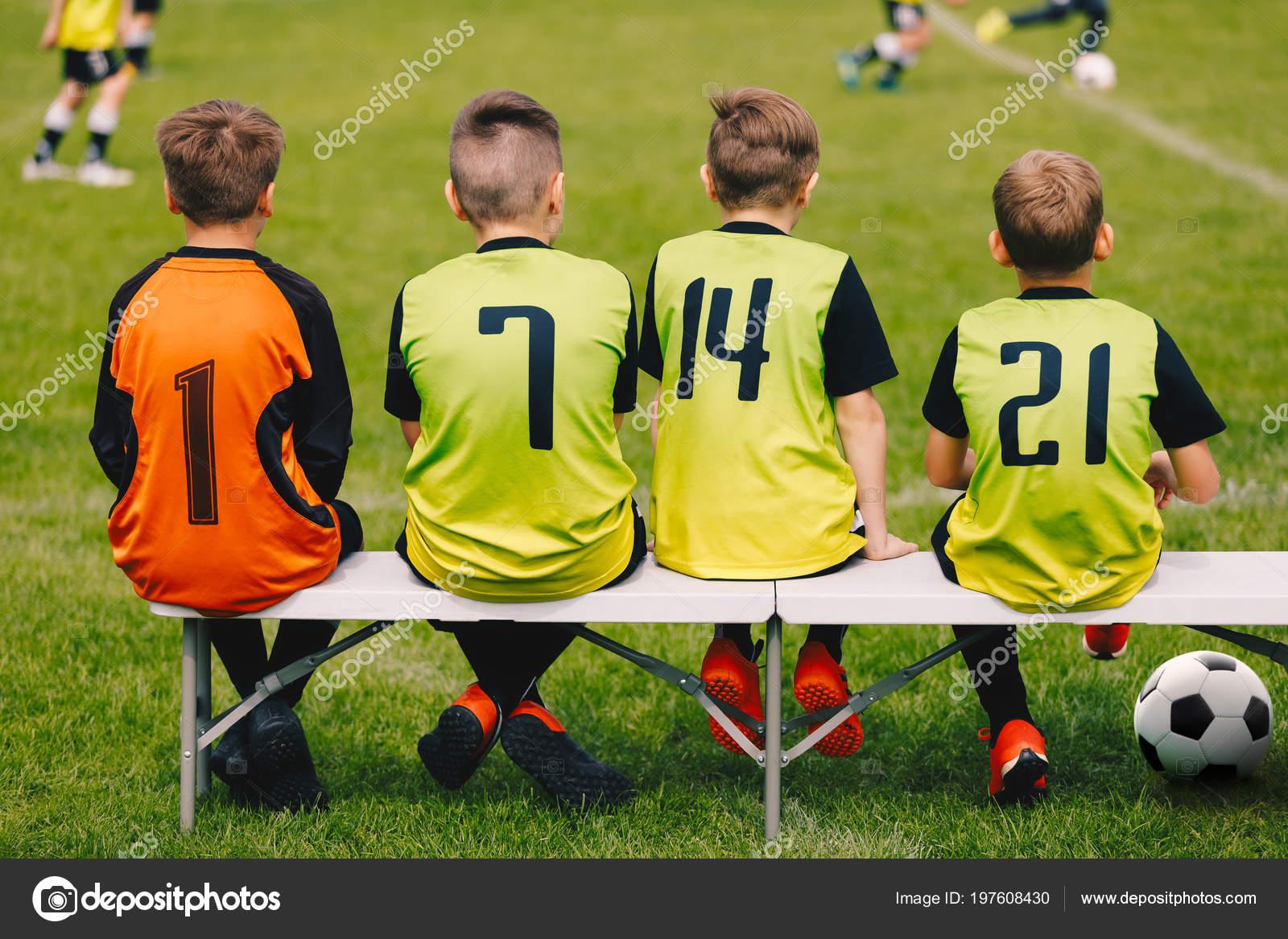 c54aa56bc11ee Equipo de fútbol de los niños sentados en un banco. Los jugadores del  equipo del balompié de los cabritos. Chicos con camisetas como un sustituto  de ...