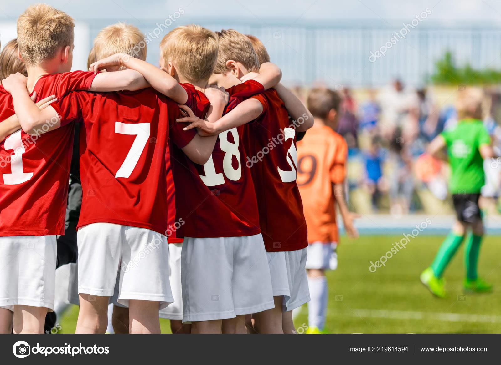 Time de futebol de meninos. Academia de futebol de crianças. Jovens  jogadores de futebol em camisas vermelhas de pé juntos em campo. 64f7d2e8e291b