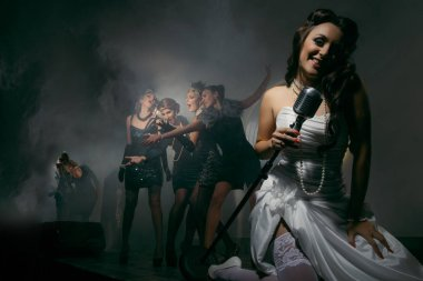 Young Singer bride with microphone and group of young women celebrating their friend`s forthcoming marriage