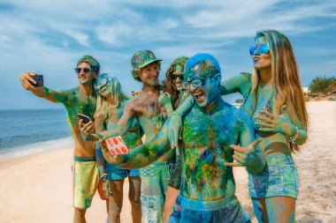 Young friends colored with color powder gulal laughing making Selfie