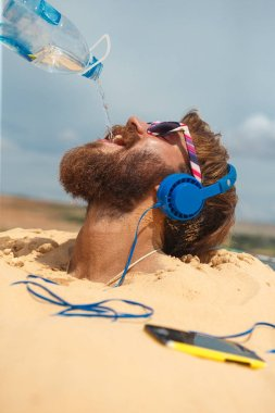 Guy with headphones buried in the sand drinking water from bottle over his head