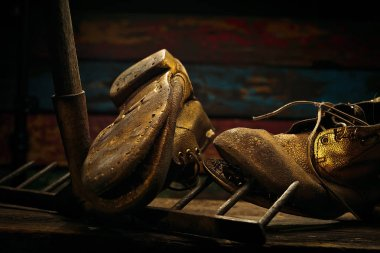 Close view of old boots and rake on wood background