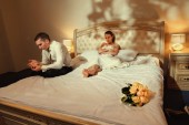 Fotografie Wedding shot of bride and groom sitting on a stylish bed