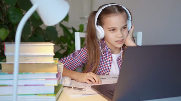teen girl in headphones listens to lesson, distance online learning home