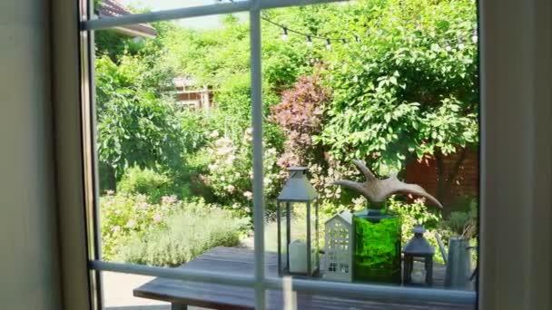výhled z okna na zahradu. dívka je zdobena květinovým stolem ve dvoře.