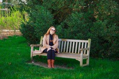 girl in coat sitting on bench in spring Park. walks in outdoors.