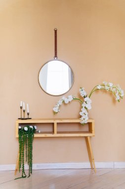 table with flowers, round mirror hanging on wall